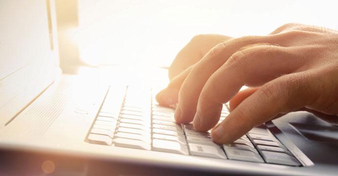 Photo d'une main posée sur un clavier d'ordinateur